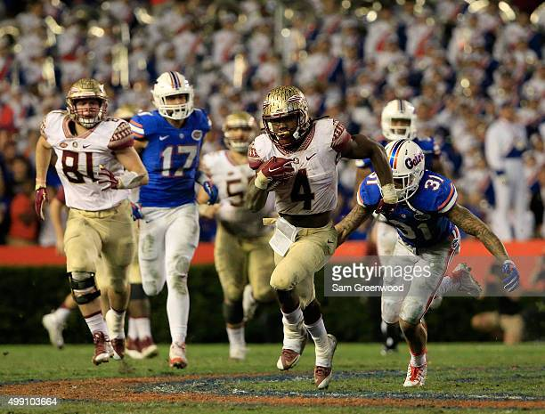 Dalvin Cook of the Florida State Seminoles runs for yardage during the game against the Florida Gators at Ben Hill Griffin Stadium on November 28...