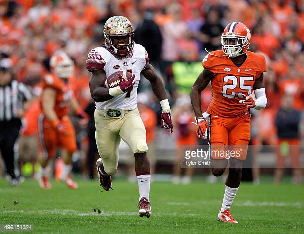 Dalvin Cook of the Florida State Seminoles rushes for a first down past Cordrea Tankersley of the Clemson Tigers during a game at Memorial Stadium on...