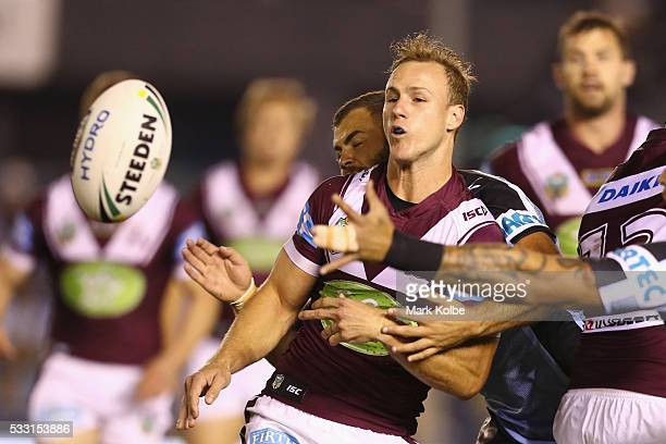 Daly CherryEvans of the Eagles passes as he is tackled by Wade Graham of the Sharks during the round 11 NRL match between the Cronulla Sharks and the...