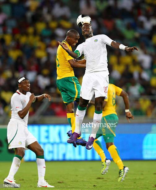 Dama Ndoye of Senegal heads the ball away from Morgan Gould of South Africa during an a friendly football match between South Africa and Senegal at...