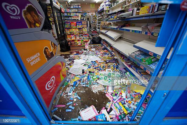 Damage is pictured to a local shop in Croydon south of London on August 9 following a third night of violence on the streets of London Violence...