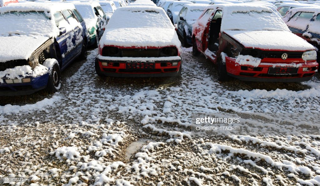 Damaged and used cars coverd with snow are pictured at a car recovery and recycling company near Munich, southern Germany, on February 6, 2013.