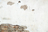 Damaged brick wall, cracked plaster. Textured background
