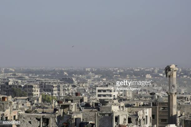 Damaged buildings and a destroyed minaret are seen as smoke rises after Assad regime forces' carried out an air strike at the Ein Terma town of...