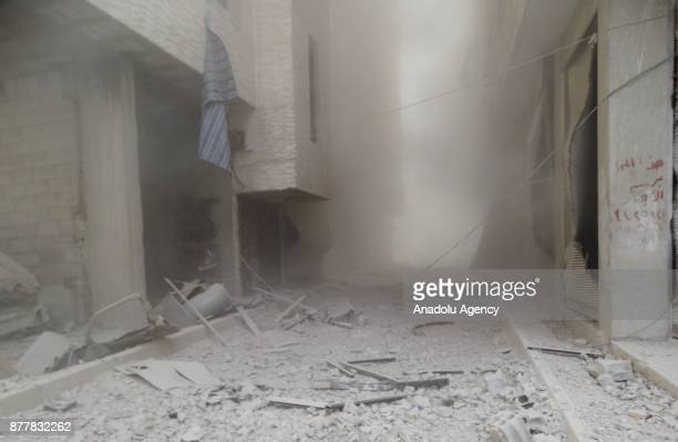 Damaged buildings are seen through the dust cloud after Assad regime's warcrafts carried out airstrikes over the deescalation zone of Ein Tarma...