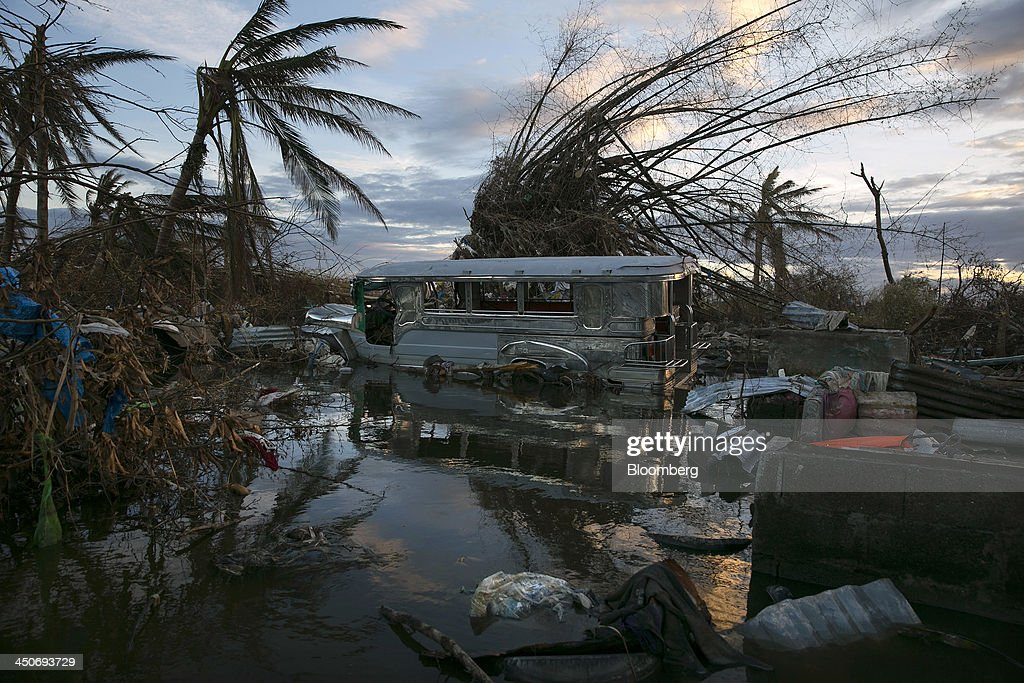 A damaged bus and other debris sit partially submerged in water in Tacloban, the Philippines, on Monday, Nov. 18, 2013. Super Typhoon Haiyan slammed into the central Philippines on Nov. 8, knocking down most buildings, killing thousands, displacing 4 million people and affecting more than 10 million. Photographer: Paula Bronstein/Bloomberg via Getty Images