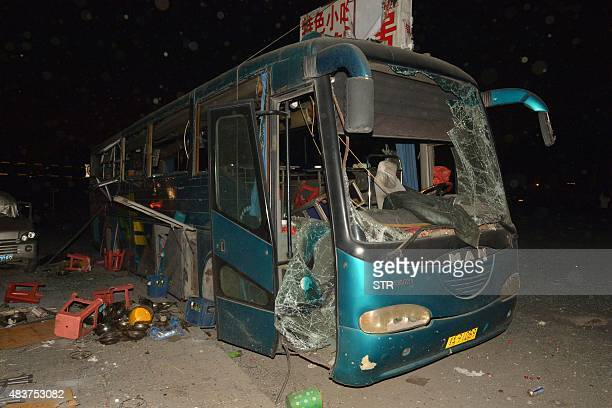 A damaged bus is seen near the site of a series of explosions in Tianjin early on August 13 2015 A series of massive explosions at a warehouse in the...
