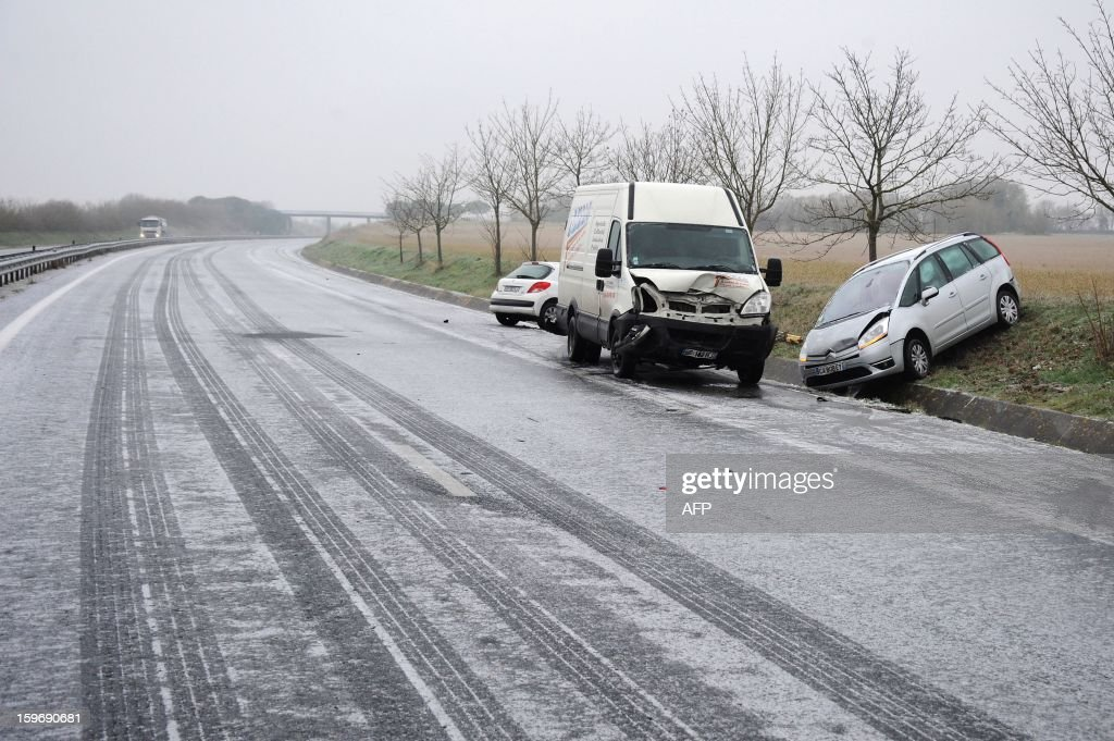 Damaged car are seen on the side of an ice-covered road after a crash due to freezing rain, on January 18, 2013 on the RN11 near Ferrieres. Thirty-seven French departments are under medium range (orange) alert due to the inclement weather.