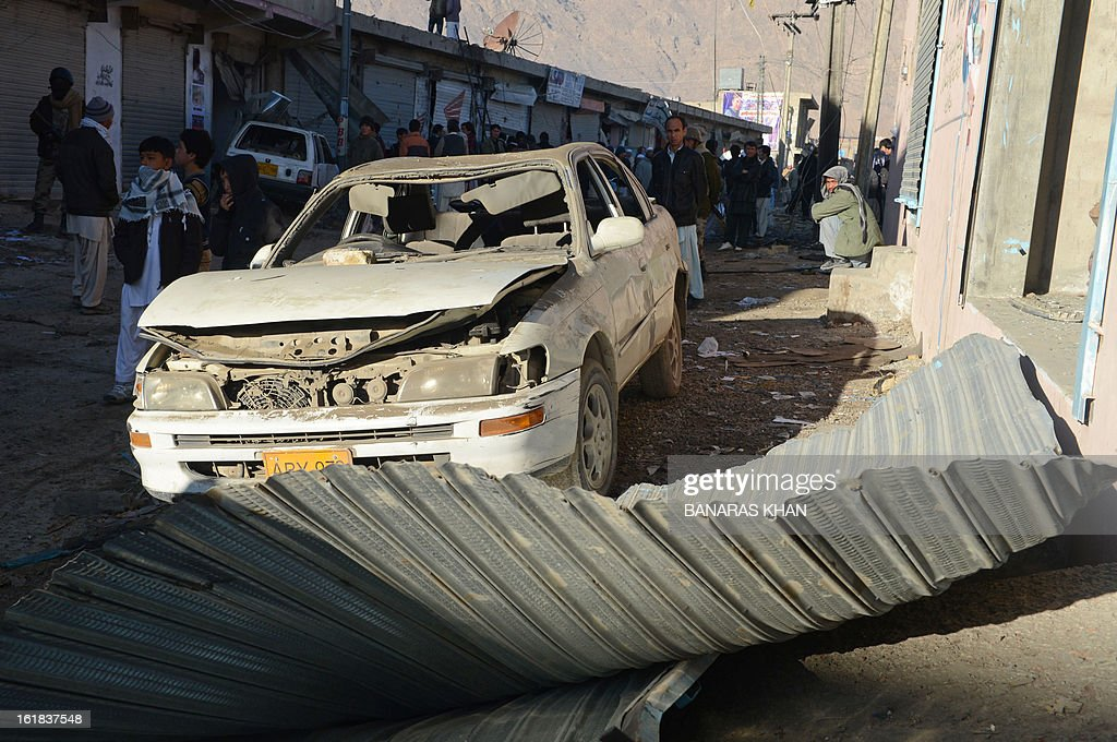 A damaged car is pictured as Pakistani Shiite Muslims look on at the scene of yesterday's bomb attack site in Quetta on February 17, 2013.The death toll from a devastating bomb attack on Shiite Muslims in southwest Pakistan rose to 81 Sunday, as the community threatened protests if swift action was not taken against the killers. AFP PHOTO/Banaras KHAN