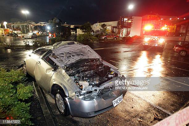 A damaged car is pictured near rescue vehicles in the North Shore of Auckland on May 3 2011 after a freak tornado hit the area killing two people and...