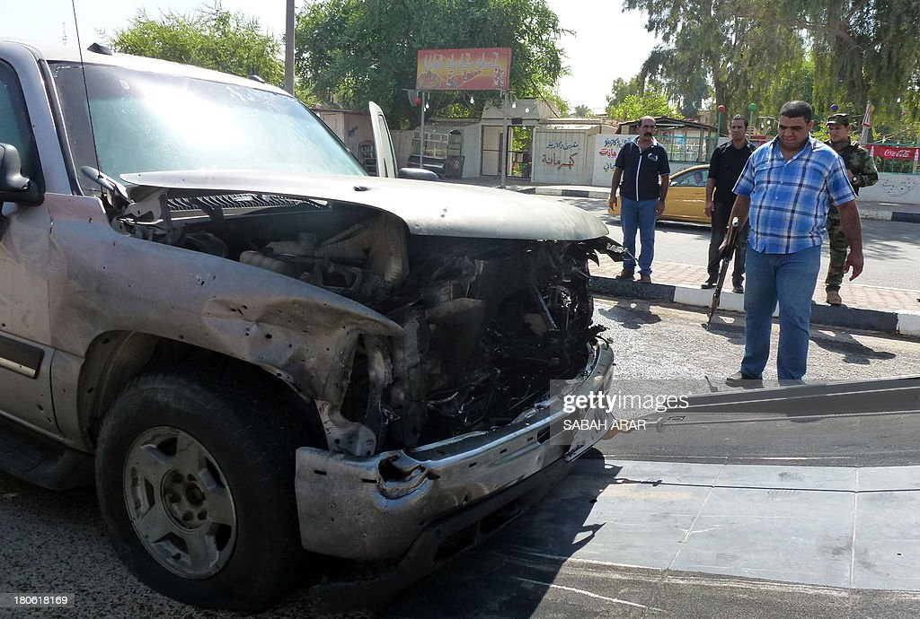 A damaged car is removed by a tow truck from the site of a car bomb attack against the convoy of Riyadh al-Adhadh, the chief of the provincial council and a Sunni lawmaker belonging to the party of the national parliament speaker on September 15, 2013 in the Waziriyah neighbourhood of north Baghdad. The car bomb killed two people and wounded four others, according to police and a medical source. AFP PHOTO SABAH ARAR
