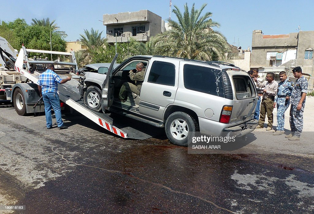 A damaged car is removed by a tow truck from the site of a car bomb attack against the convoy of Riyadh al-Adhadh, the chief of the provincial council and a Sunni lawmaker belonging to the party of the national parliament speaker on September 15, 2013 in the Waziriyah neighbourhood of north Baghdad. The car bomb killed two people and wounded four others, according to police and a medical source.