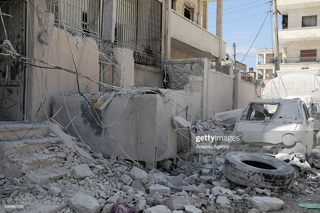 A damaged car is seen in front of the debris of a building after the Russian airstrikes targeted Sevra district of Idlib in Syria on May 31, 2016.