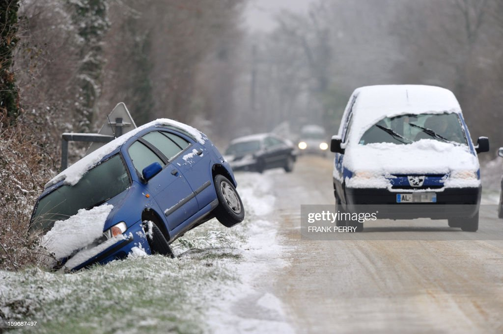 A damaged car is seen on the side of a ice-covered road on January 18, 2013 near Vigneux-de-Bretagne, Brittany, western France. Thirty-seven French departments are under medium range (orange) alert due to the inclement weather. AFP PHOTO / FRANK PERRY.