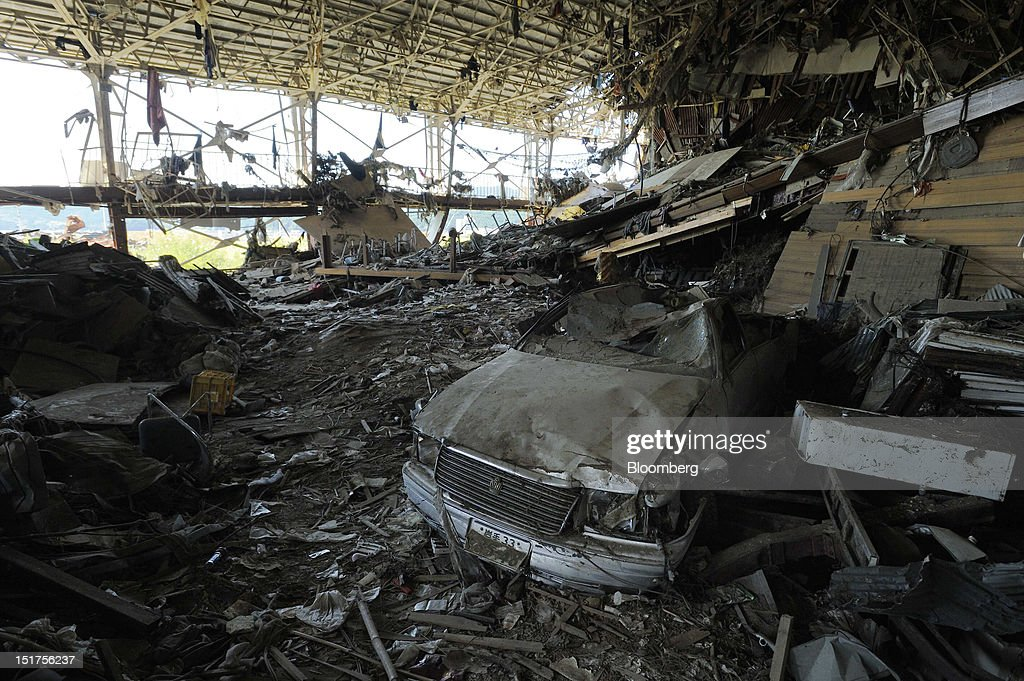 A damaged car sits in a pile of debris in the gymnasium of a high school in an area damaged by last year's March 11 earthquake and tsunami in Rikuzentakata City, Iwate Prefecture, Japan, on Friday, Sept. 7, 2012. Japan's economy expanded in the second quarter at half the pace the government initially estimated, underscoring the risk of a contraction as Europe's debt crisis caps exports. Photographer: Akio Kon/Bloomberg via Getty Images