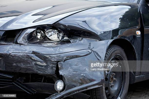 Damaged car with distorted reflection of town
