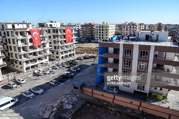 TOPSHOT Damaged cars and apartments on which Turkish flags are displayed are seen at the blast site on February 18 2017 at Viransehir in Sanliurfa...