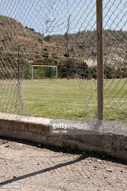 Damaged chainlink fence against soccer field