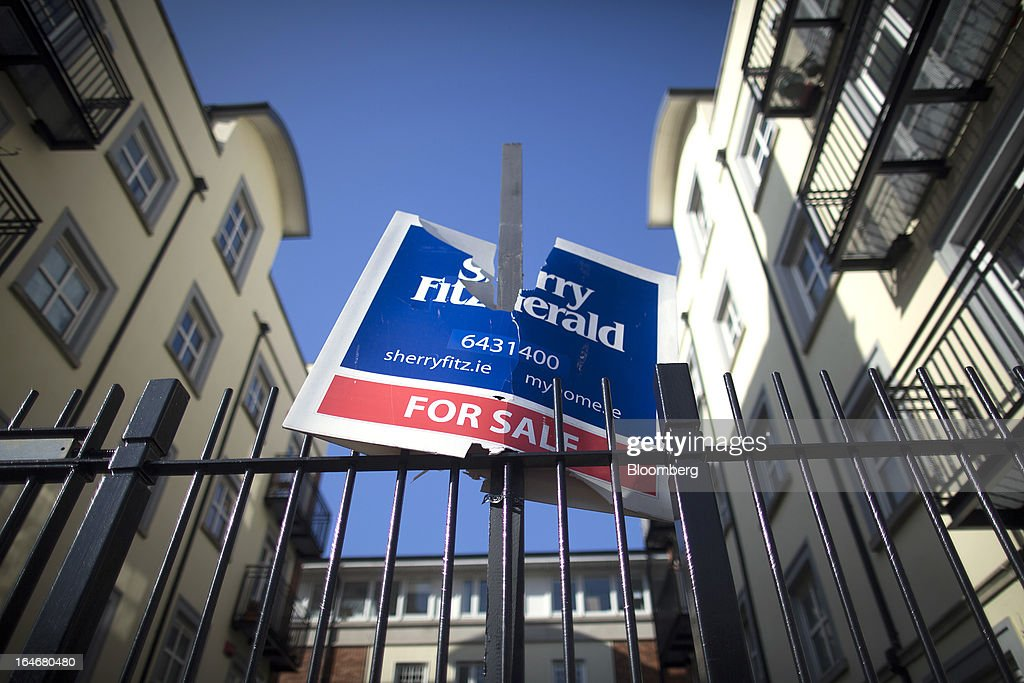 A damaged estate agent's board advertising a residential apartment 'For Sale' sits a on railings outside the housing complex in Dublin, Ireland, on Saturday, March 16, 2013. Ireland's renewed competiveness makes it a beacon for the U.S. companies such as EBay, Google Inc. and Facebook Inc., which have expanded their operations in the country over the past two years. Photographer: Simon Dawson/Bloomberg via Getty Images