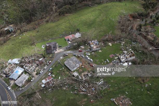 Damaged homes and downed trees are seen as people deal with the aftermath of Hurricane Maria on September 25 2017 in Corozal Puerto Rico Maria left...