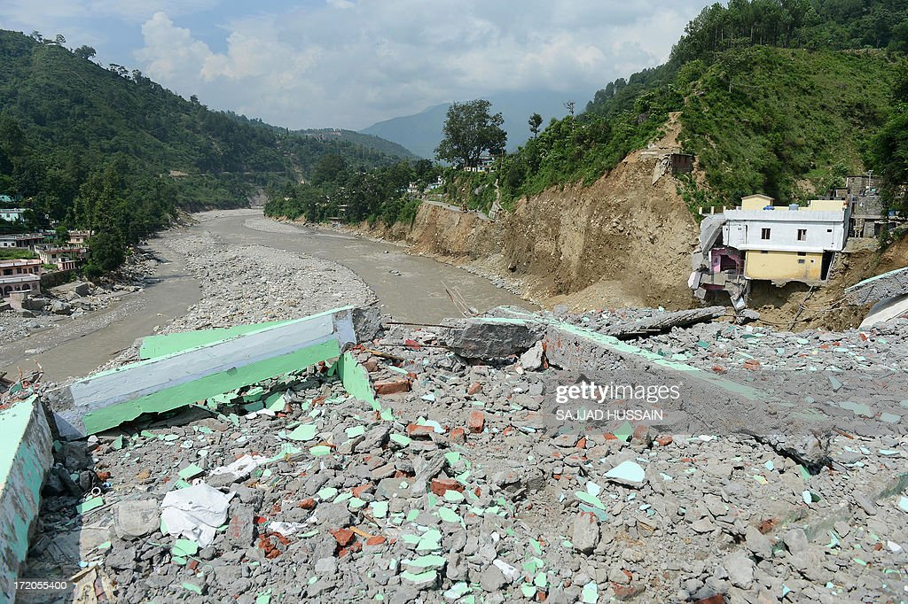 A damaged house is perched on the mountainside alongside a destroyed road at Silli, in the flood affected area of northern Uttarakhand state on July 1, 2013. Construction along river banks will be banned in a devastated north Indian state amid concerns unchecked development fuelled last month's flash floods and landslides that killed thousands, the state's top official said July 1.