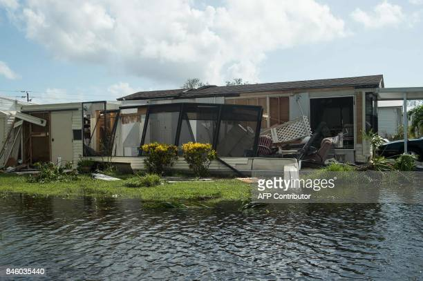 A damaged house is seen in a flooded street at the Enchanted Shores manufactured home park in Naples Florida on September 11 2017 after Hurricane...