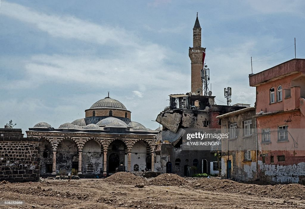 Damaged houses and a mosque are pictured in the historical district in Diyarbakir, southeastern Turkey, on May 5, 2016, following clashes between Turkish forces and Kurdish militants. / AFP / ILYAS