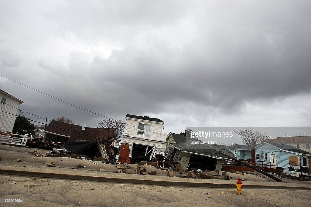 Damaged houses sit on a street on October 30, 2012 in the Breezy Point Neighborhood of the Queens borough of New York City. At least 40 people were reportedly killed in the U.S. by Sandy as millions of people in the eastern United States have awoken to widespread power outages, flooded homes and downed trees. New York City was hit especially hard with wide spread power outages and significant flooding in parts of the city.