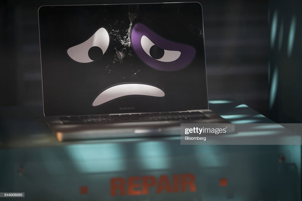 A damaged laptop computer is displayed in the window of the Tekserve store on 23rd Street in New York, U.S., on Thursday, June 30, 2016. New York City's original Apple repair store, Tekserve, is closing, succumbing to competition and rising rents after almost 30 years of servicing computers and providing technical support to local residents. Photographer: Victor J. Blue/Bloomberg via Getty Images