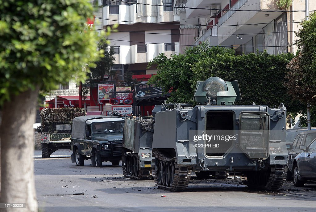 Damaged Lebanese army vehicles are seen near the mosque where Sunni cleric Sheikh Ahmad al-Assir preaches to carry the wounded from the area of clashes in the district of Abra, near the southern Lebanese city of Sidon, on June 24, 2013. At least sixteen soldiers have been killed in clashes with supporters of al-Assir in southern Lebanon, the army said, in violence tied to rising sectarian tensions fanned by the Syria conflict.