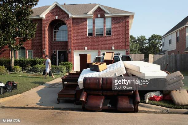 Damaged possession are left at the curb as residents recover from damage to their homes after torrential rains caused widespread flooding during...