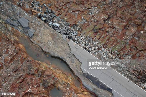 A damaged road is seen atop the Oroville Dam in Oroville California on February 13 2017 Almost 200000 people were under evacuation orders in northern...
