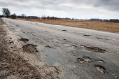 Badly damaged country asphalt road after winter