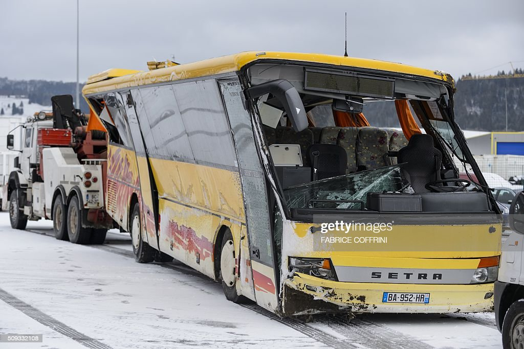 A damaged school bus is towed away in Pontarlier, after it crashed on a motorway in Montbenoît, eastern France, on February 10, 2016. Two persons were killed and four slightly injured, after the school bus went off the road presumably due to bad weather conditions, according to the police. The accident occurred at around 7:30 a.m. on Wednesday, when it was on its way to the Lucie Aubrac college in the Doubs region. / AFP / FABRICE COFFRINI