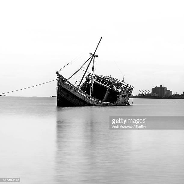 Damaged Ship Sinking In Sea Against Clear Sky