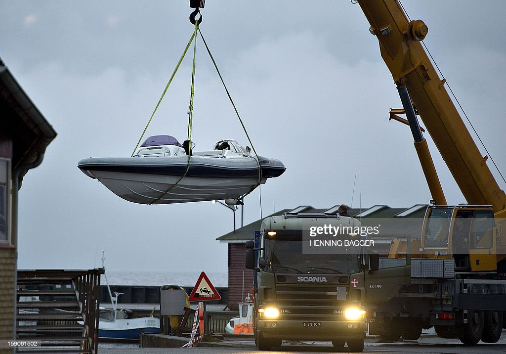 A damaged speedboat is hoisted out of the water at the harbour of the the small town of Aalbaek on January 7, 2013 at the northern top of peninsula Jutland, 25 miles from the Norwegian coast. Danish police say one man was killed one was wounded and a third suspect arrested in a shootout involving the boat, after police surprised the three Norwegian men with 250 kilos of hashish. AFP PHOTO / SCANPIX DENMARK - Henning Bagger