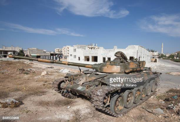 A'ZAZ ALEPPO SYRIA A damaged tank is parked near a MIG bombed building in A'zaz Syria