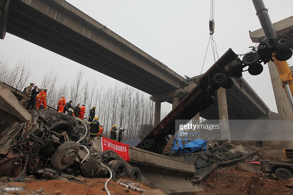 A damaged truck (R) is moved by rescuers at the scene of the collapsed Yichang bridge near the city of Sanmenxia, central China's Henan province, on February 1, 2013 after a fireworks-laden truck exploded as it crossed the bridge killing 26 people as the structure collapsed and vehicles plummeted to the ground, state-run media reported. An 80-metre long part of the bridge collapsed and six vehicles had been retrieved from the debris, China's official news agency Xinhua said. The bridge near the city of Sanmenxia is on the G30 expressway, the longest road in China, which stretches for nearly 4,400 kilometres (2,700 miles) from China's western border with Kazakhstan to the eastern Yellow Sea.
