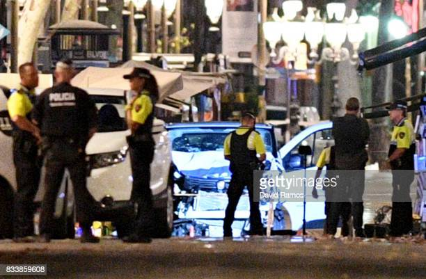 A damaged van believed to be the one used in the attack is surrounded by police officers in the Las Ramblas area on August 17 2017 in Barcelona Spain...
