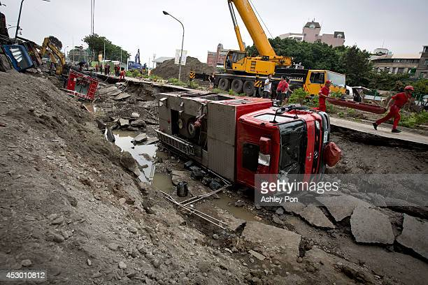 Damaged vehicles lie on the road after gas explosions in southern Kaohsiung on August 1 2014 in Kaohsiung Taiwan A series of powerful gas blasts...