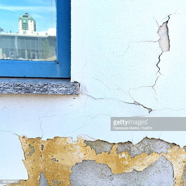 Damaged White Wall With Building Reflection On Window Glass