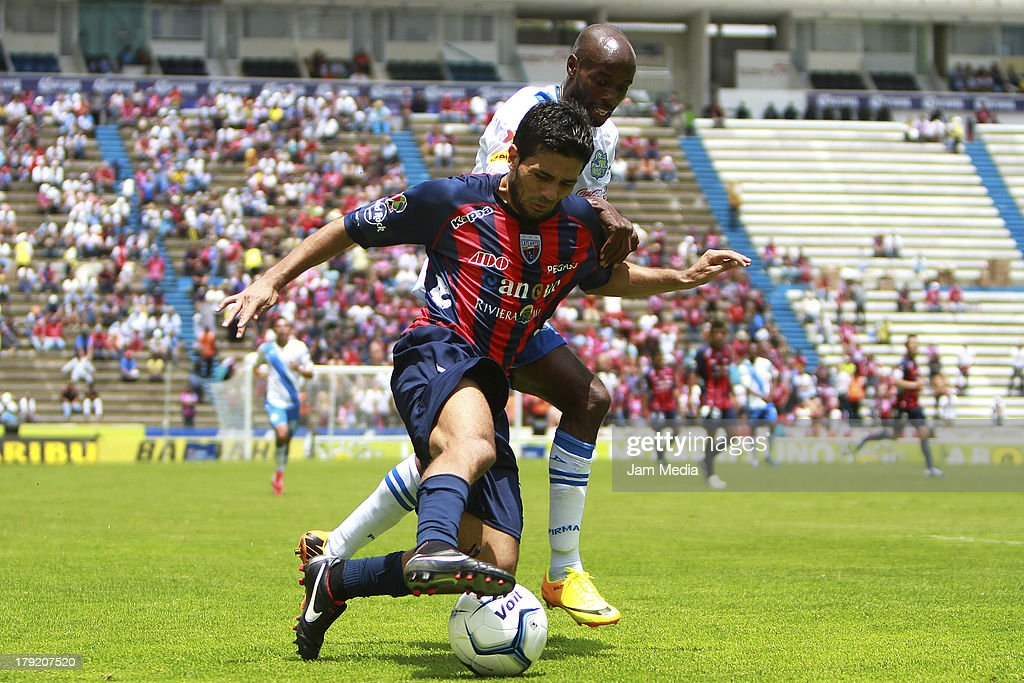 Damarcus Beasley (L) of Puebla struggles for the ball with Walter Erviti (R) of Atlante during a match between Puebla and Atlas as part of the Apertura 2013 Liga Bancomer MX at Cuahtemoc Stadium on september 01, 2013 in Puebla, Mexico.