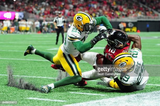 Damarious Randall and Kentrell Brice of the Green Bay Packers tackle Taylor Gabriel of the Atlanta Falcons during the first half at MercedesBenz...
