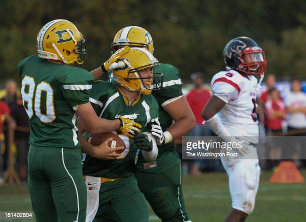 Damascus High School quarterback Chase Williams with ball is congratulated after scoring on a one yard touchdown run during the game between the...