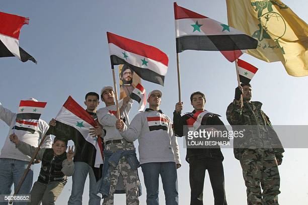 Syrian people hold up their national flag and the yellow flag of Lebanese Shiite militia Hezbollah as they demonstrate in Damascus in support of the...