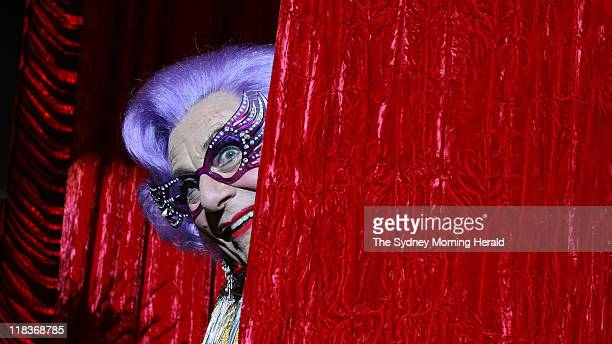 Dame Edna Everage peeks out from behind the red curtain during a photo call for her latest show 'Barry Humphries Back With A Vengeance' which opens...
