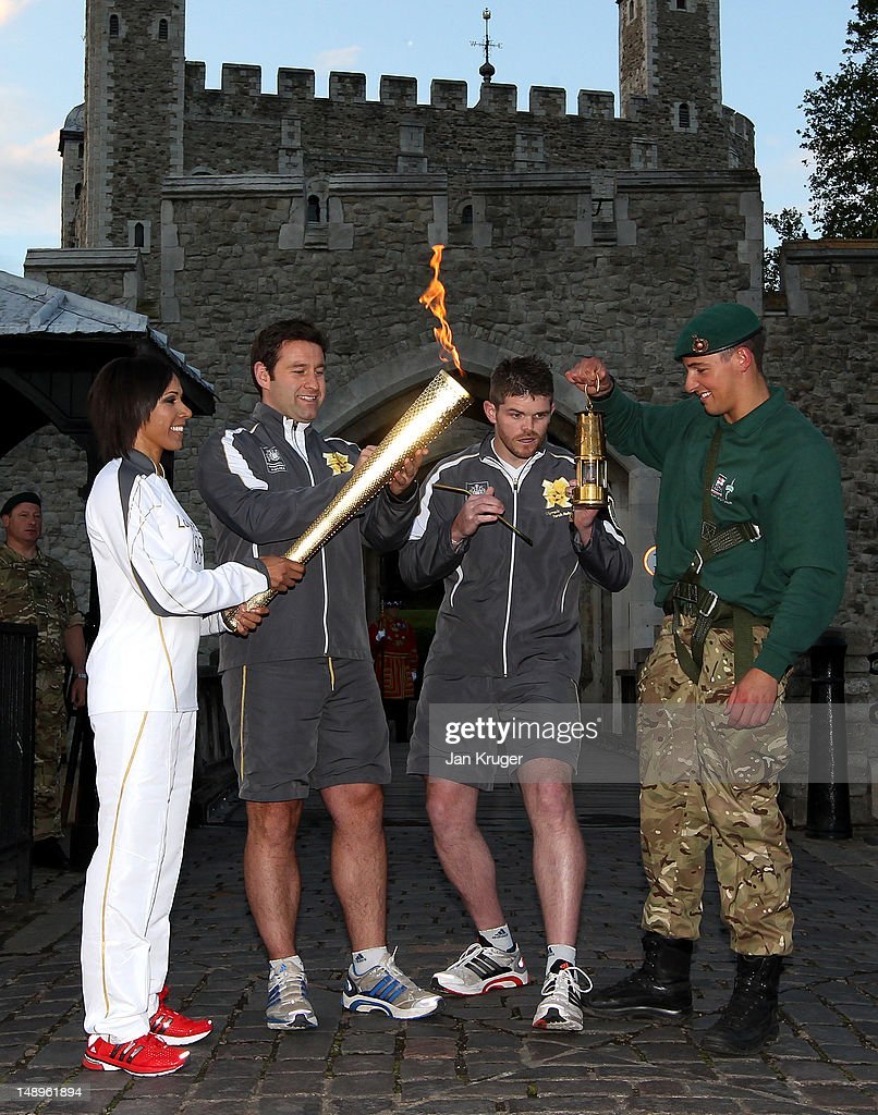Dame <a gi-track='captionPersonalityLinkClicked' href=/galleries/search?phrase=Kelly+Holmes&family=editorial&specificpeople=213496 ng-click='$event.stopPropagation()'>Kelly Holmes</a> lights her torch as Marine Martyn Williams holds the flame during the London 2012 Olympic Torch Relay on July 20, 2012 in London, England. The Olympic Flame is now on day 63 of a 70-day relay involving 8,000 torchbearers covering 8,000 miles.