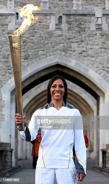 Dame Kelly Holmes poses with the Olympic Torch in the Tower of London during the London 2012 Olympic Torch Relay on July 20 2012 in London England...
