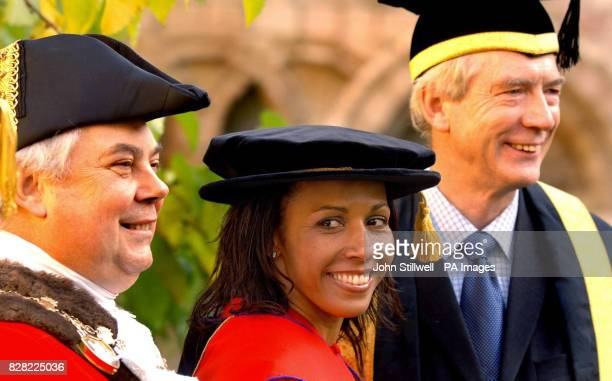 Dame Kelly Holmes the double Olympic gold medal winner smiles as she poses with university officials before receiving an honorary degree as Doctor of...