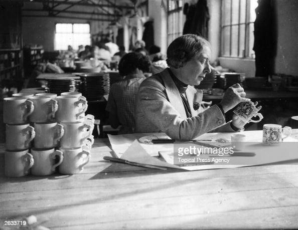 Dame Laura Knight painter of stage and circus life putting the finishing touches to the Coronation mugs she has designed at a StokeonTrent pottery